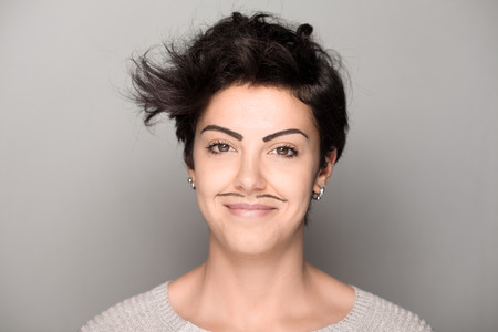 mujeres morenas: Smiling Woman with Drawn Mustaches on Gray Background