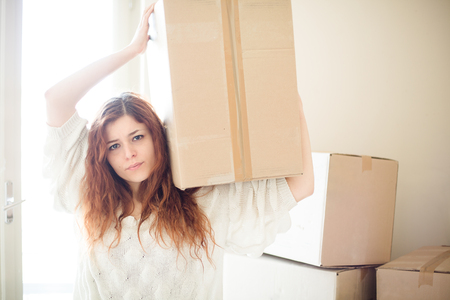 multiple: Tired Redhead Woman Moving, Holding a Box on Her Shoulder Stock Photo