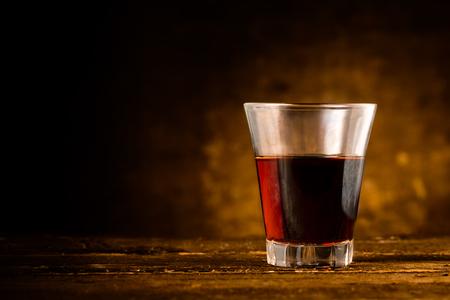 Shot of Alcoholic Bitter Liquor on Wooden Surface Standard-Bild