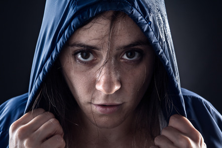 tired: Sweaty Woman with Blue Raincoat Holding a Hood Stock Photo