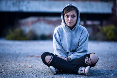 Woman with Sweatshirt and Torn Trousers Sitting on the Street Stock Photo