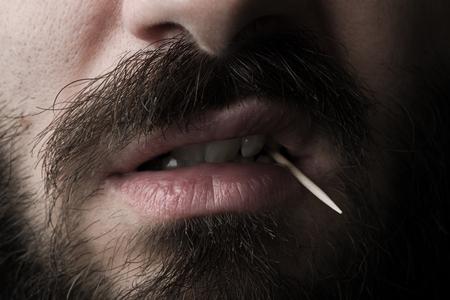 木のつまようじであごひげの男の口を閉じる 写真素材