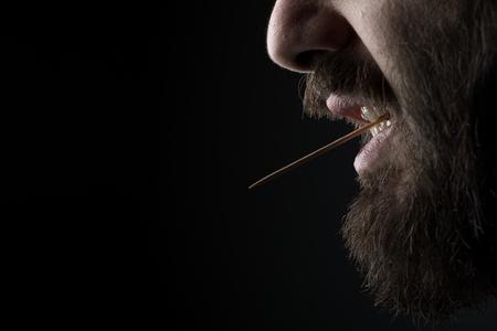黒い背景に彼の口の中に木のつまようじを持つひげの男のクローズアップ