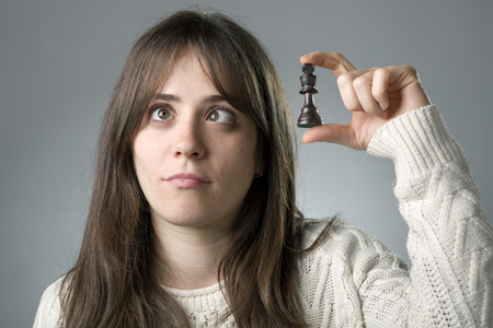 Squint Woman Holding a King Chess Pieces