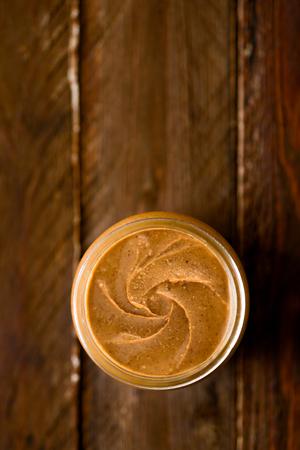 Peanut Butter in a Glass Jar on Wood