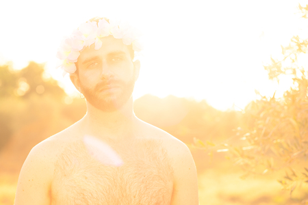 Man with Flowers Crown and Naked Chest at Sunset
