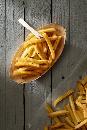 French Fries on Paper Bowl with Wooden Fork