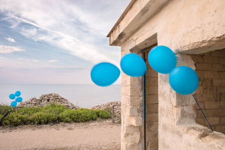 Blue Balloons Tied on a Ruined House with Seascape 写真素材
