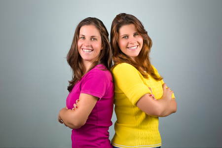 Two Twin Sisters with Arms Crossed