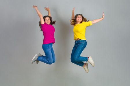 Two Twin Sister Jumping on Gray Background