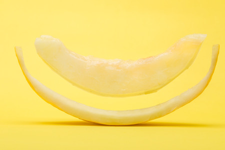 Floating Slice of Canary Melon on Yellow Background 写真素材