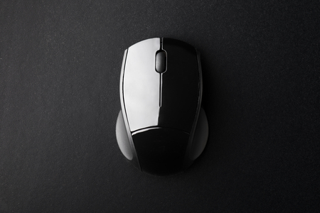 Black Wireless Optical Mouse on Black Surface Seen from Above