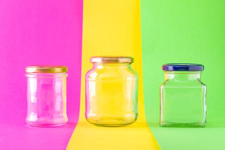 Three Empty Glass Jars on Multicolored Background