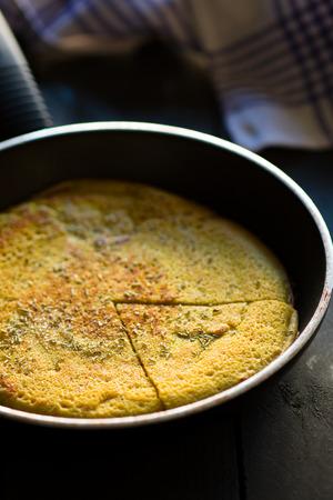 Sliced Vegan Chickpea Omelette On a Frying Pan