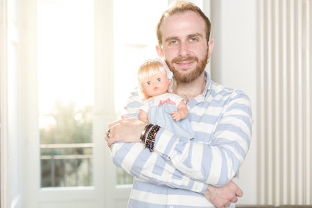 Smiling Redhead Man with Beard  Hugging a Doll