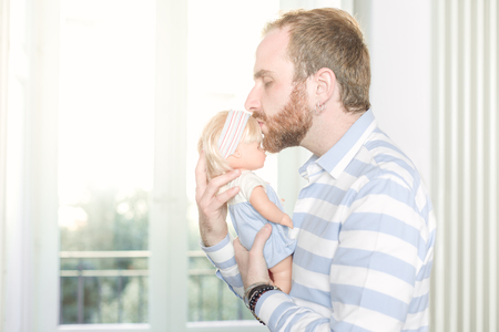 Redhead Man with Beard Kissing a Doll On Its Forehead 写真素材 - 121121012