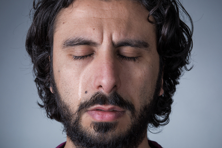 Man with Beard and Long Hair Crying with Closed Eyes