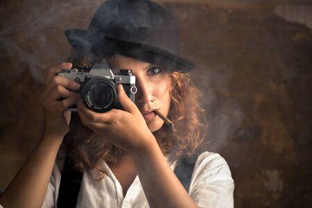 Fotografin mit Bowler und Hosenträgern, die eine Zigarre rauchen Standard-Bild