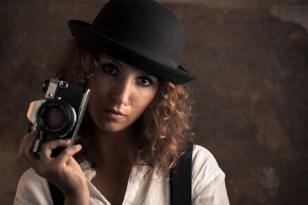 Woman Photographer with Bowler and Suspenders Holding a Camera 写真素材 - 135402823