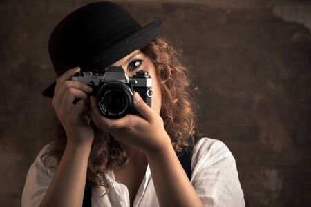 Woman Photographer with Bowler and Suspenders Holding a Camera
