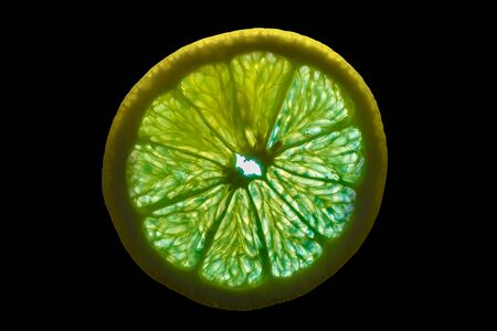 Slice of Lemon with Backlight Isolated on Black Background 写真素材