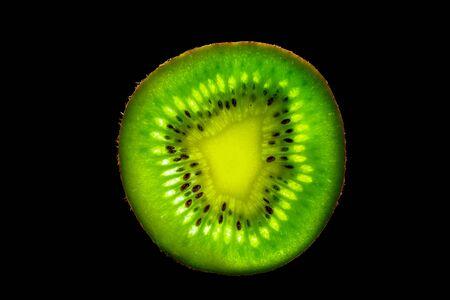 Slice of Kiwi with Backlight Isolated on Black Background 写真素材 - 135402853