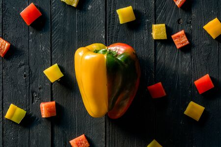 Red And Yellow Peppers Sliced on Black Wooden Surface
