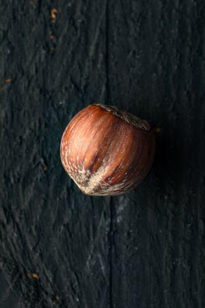 Hazelnut on a Black Wooden Surface 写真素材