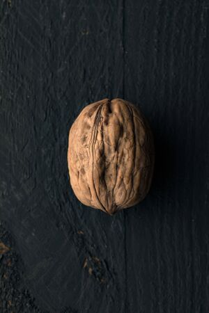 One Walnut on a Black Wooden Surface