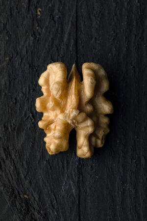 One Walnut Kernel on a Black Wooden Surface