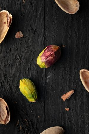 Pistachio on a Black Wooden Surface with Scattered Nutshell Pieces