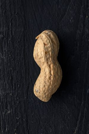 Close Up of a Peanut on Black Wooden Surface
