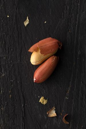 Two Peanuts on Black Wooden Surface