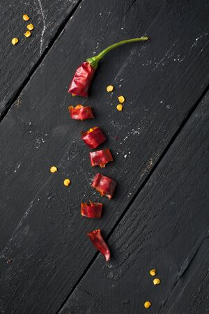 Dried Red Chili Pepper Cut to Pieces on Black Wooden Table