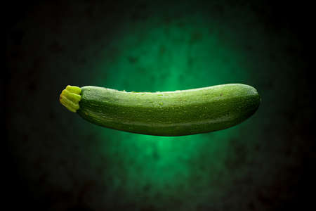 Wet Courgette Floating with Green Background 写真素材