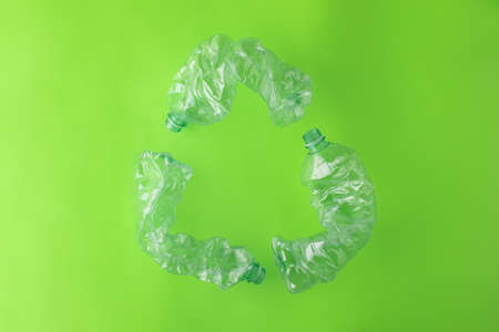Recycling Symbol Made with Three Plastic Bottles on Green Background 写真素材