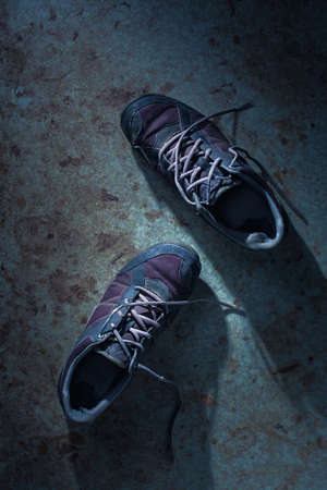 Two Old Worn Out Sneakers on Dirty Surface