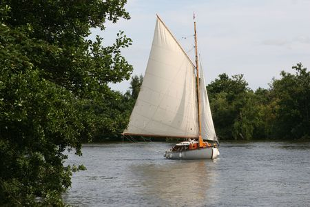 A boat tacks through the Norfolk Broads Stock Photo