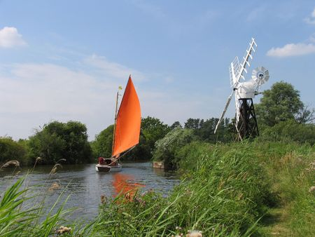 A sailboat passes a windmill