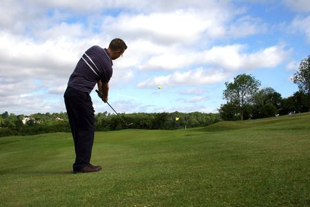 A junior golf champion lifts a shot onto the green