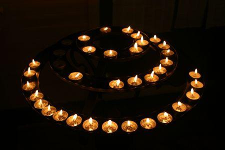 Un círculo concéntrico de los canales de las velas en una iglesia en la noche Foto de archivo - 336375
