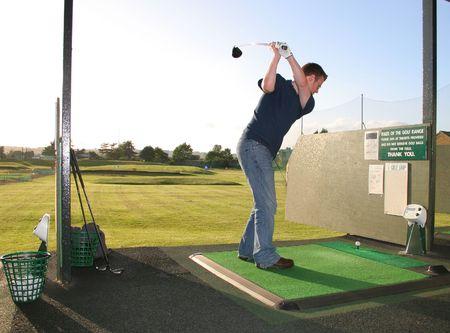 A junior golf champion practices on the golf range