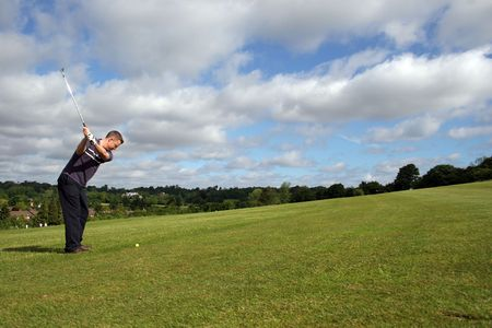 A junior golf champion prepares to lift the ball to the green Stock Photo