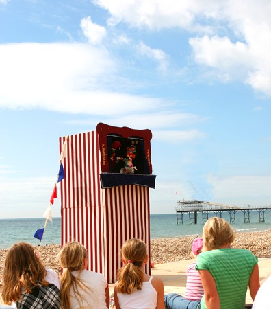 Children watch an old fashioned Punch and Judy Show by the sea