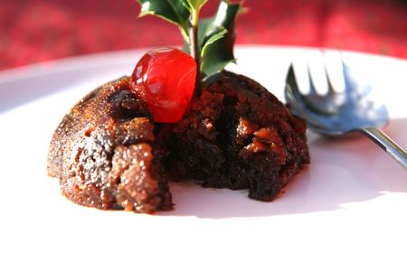 A delicious cherry sits on a Christmas Pudding