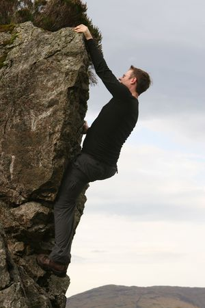 A young  free climber reaches the summit of a scottish mountain climbing without ropes at 5,000 feet Stock Photo
