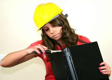 A pretty teen girl fixes her laptop computer with a large pair of pliers. Stock Photo
