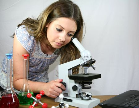 A biology student uses her microscope and laptop computer