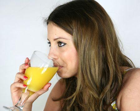 A pretty girl drinks a glass of orange juice Stock Photo
