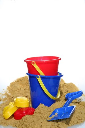 A holiday image of buckets and spades with sand from a beach photo